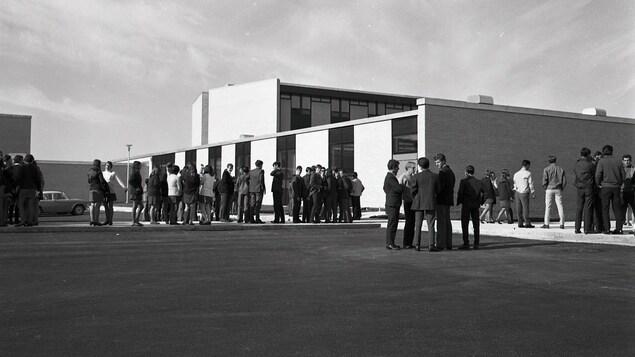 Photo en noir et blanc. Gens devant un bâtiment.