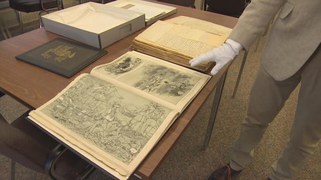 Un vieux livre est ouvert sur une table et manipulé par une main gantée.