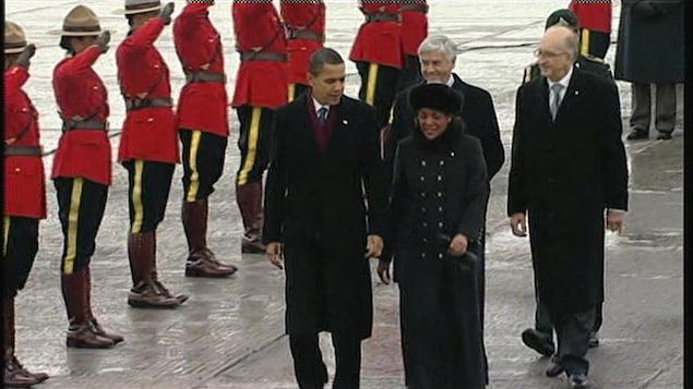 Barack Obama marche sur la piste de l'aéroport  pendant que plusieurs officiers de la Gendarmerie Royale du Canada sont au garde-à-vous.