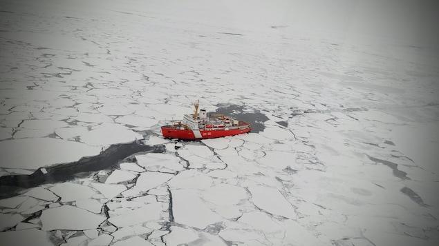 vue aérienne d'un bateau naviguant dans une mer de glace.