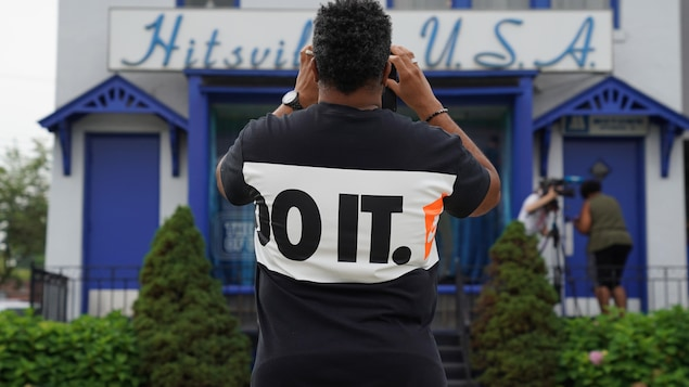 Un homme prend une photo du Musée Motown sur lequel est écrit «Hitsville USA».