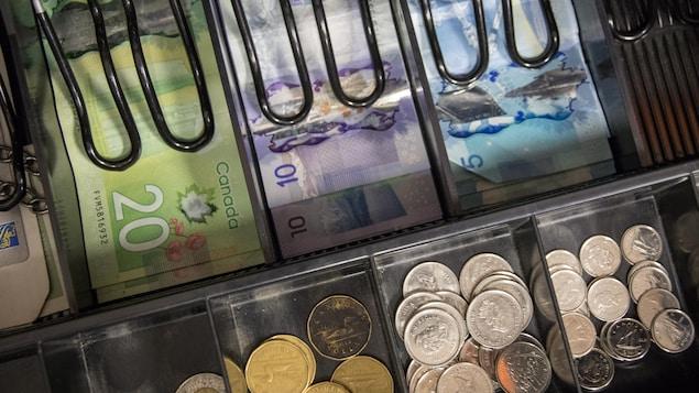Vue de l'intérieur d'une caisse enregistreuse, remplie de billets et de pièces de monnaie.
