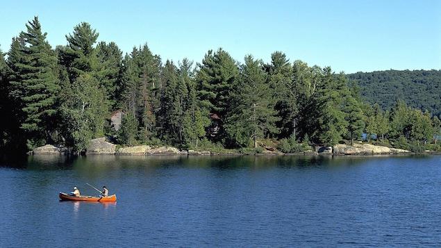 Deux hommes à la pêche dans un canot sur un lac.