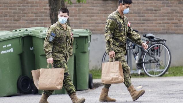 Des membres des Forces armées canadiennes transportent des sacs bruns.