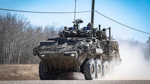Un véhicule militaire roule sur une route de graviers.