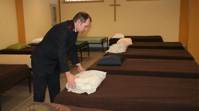 Un homme préparant des lits dans un refuge.