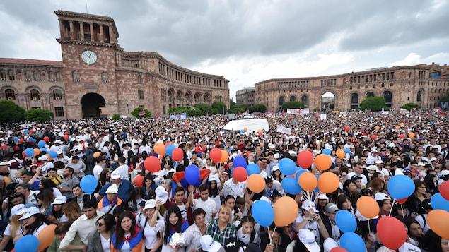 Des milliers de personnes sont rassemblées dans une place centrale de la capitale. La foule compte de très nombreux jeunes, et plusieurs manifestants sont vêtus de blanc.