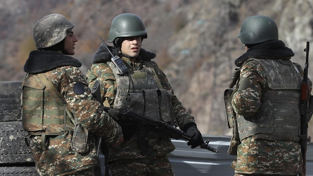 Des militants armés et habillés en tenues militaires.