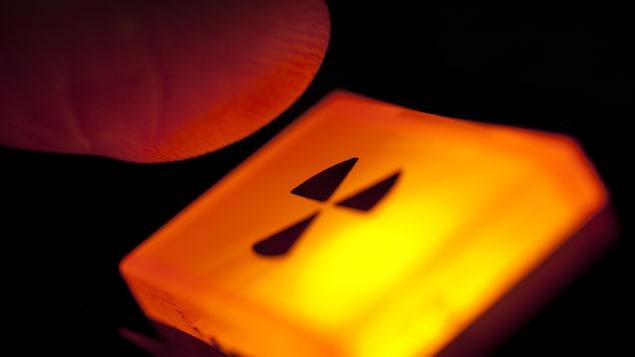 Un bouton illuminé fait apparaître le symbole de la radioactivité.