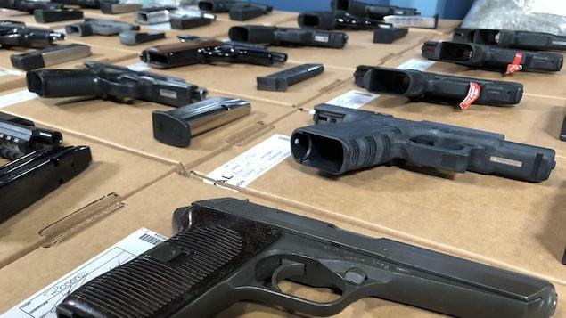 Gros plan sur des armes de poing disposés sur une table.