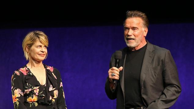 L'actrice Linda Hamilton et l'acteur Arnold Schwarzenegger tenant des microphones sur scène lors d'une présentation en avril 2019 à Las Vegas.