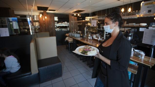 Une jeune femme portant un couvre-visage se dirige vers des convives avec une assiette remplie de nourriture.