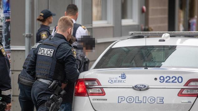 Des policiers font rentrer un homme dans une voiture du Service de police de la Ville de Québec.