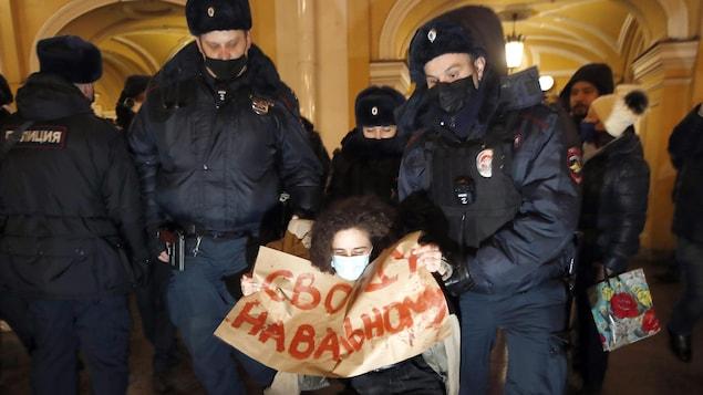 Des policiers arrêtent une femme.