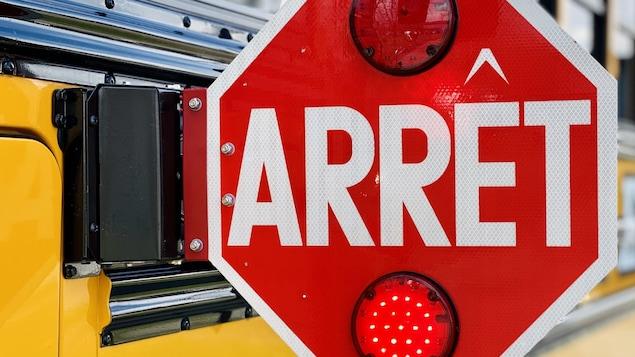 Gros plan sur une pancarte d'arrêt d'un autobus scolaire déployée.