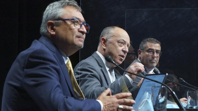 Trois hommes assis à une table en conférence de presse.