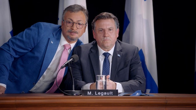 Un homme debout et un homme assis devant un micro, dans une conférence de presse.