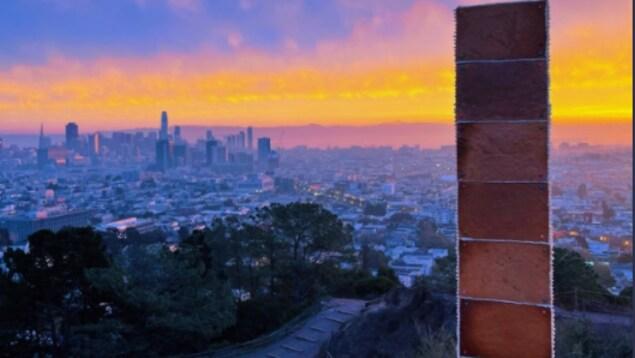Une tour en pain d'épices au sommet d'une colline au lever du Soleil devant la ville de San Francisco au bas.