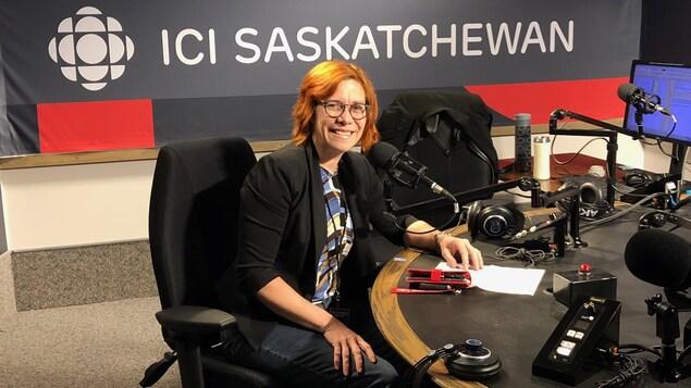 Une femme pose devant la caméra dans les studios de radio d'Ici Saskatchewan
