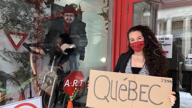 Une femme se tientdevant une vitrine où un artiste est assis sur un vélo stationnaire, elle tient une pancarte avec le mention « Québec, 230 km ».