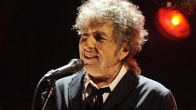 Bob Dylan sourit devant un micro.