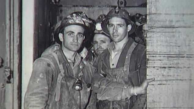 Groupe de mineurs avec leurs habits qui descendent à la mine.