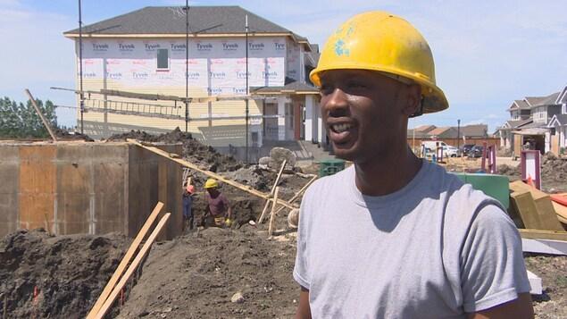 Un homme portant un chapeau de construction sourit devant un chantier de construction où s'affairent deux autres hommes.