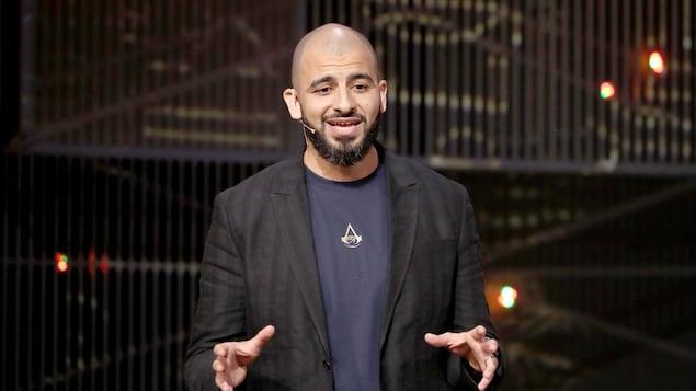 Un homme s'exprime sur une scène.