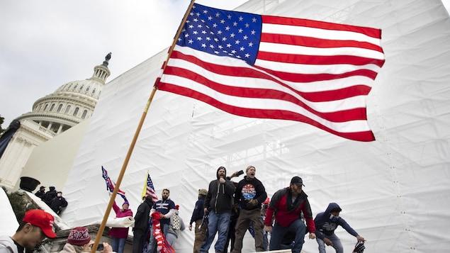 Des partisans de Donald Trump crient à l'extérieur du Capitole, où se trouve un immense drapeau américain.