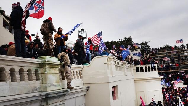Des partisans de Donald Trump, à l'extérieur du Capitole, certains portant des drapeaux américains ou pro-Trump, qu'ils ont pris d'assaut.