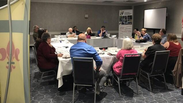 Des députés communautaires de l'Assemblée communautaire fransaskoise assis autour d'une table dans le cadre d'une réunion.