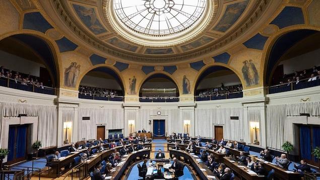 Les députés sont assis sur leurs chaises à l'intérieur de l'Assemblée législative du Manitoba