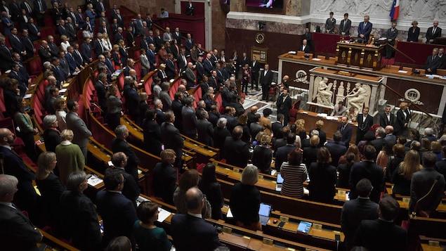 Les députés de l'Assemblée nationale française se tiennent debout.