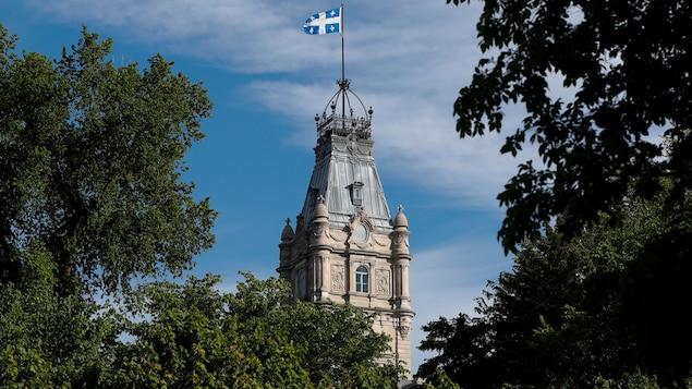 La tour coiffée du drapeau du Québec est vue à travers des arbres.