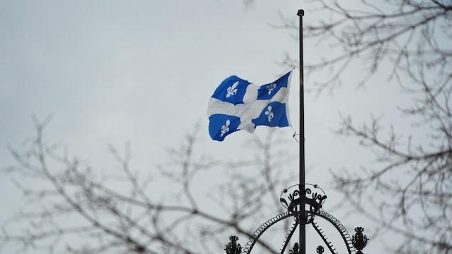 Le drapeau du Québec en berne au-dessus de l'Assemblée nationale.