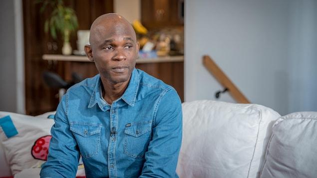 Assim Traoré est assis sur un sofa dans son salon.