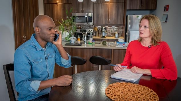 Assim Traoré parle au téléphone assis dans sa salle à manger. La journaliste Brigitte Bureau l'observe.