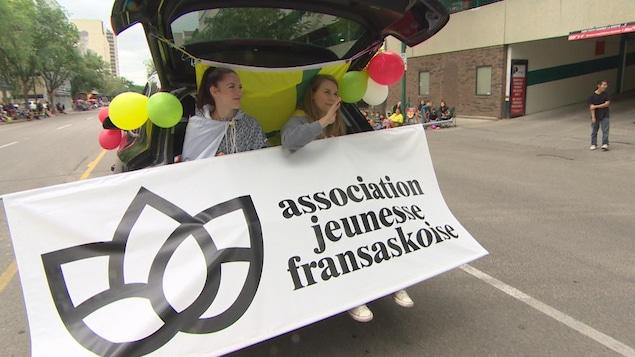 Deux jeunes femmes assises à l'arrière d'un véhicule montrent le logo de l'Asociation jeunesse fransaskoise durant le défilé.