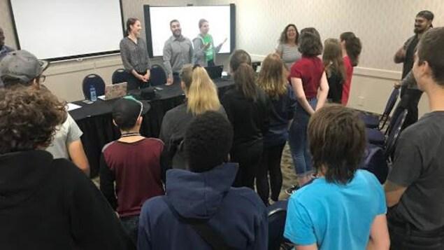 Une vingtaine de membres de l'Association jeunesse fransaskoise se tiennent debout dans une salle devant une longue table.