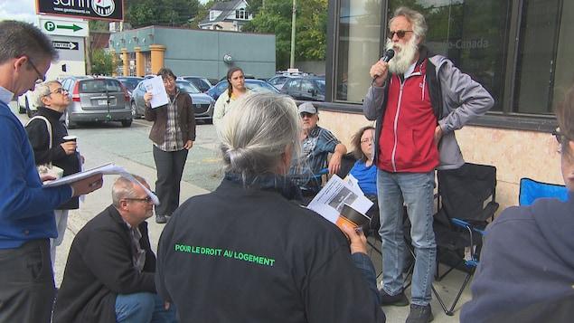 Un homme barbu s'adresse à quelques personnes avec un micro devant les bureaux de radio-canada.