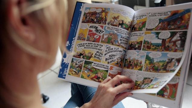 Une femme lit la bande dessinée intitulée « L'anniversaire d'Astérix et Obélix ».