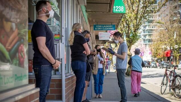Une file de gens devant une pharmacie.