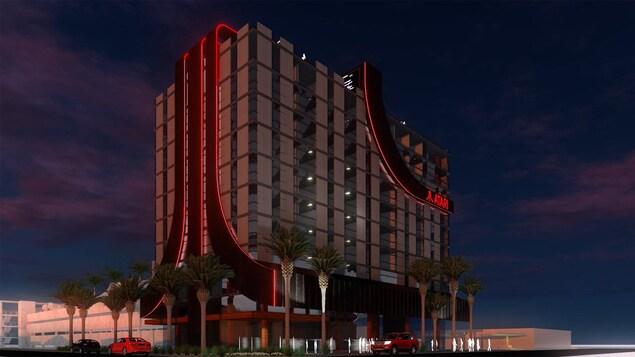 Un hôtel avec le logo d'Atari, avec quelques palmiers et des voitures devant.