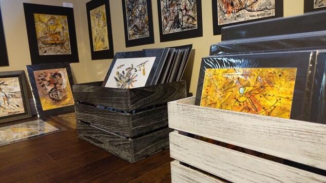 Des peintures sont entassées dans des caisses de bois