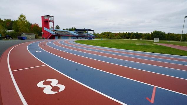 Courbe et rangées bleu et rouge de la piste d'athlétisme.