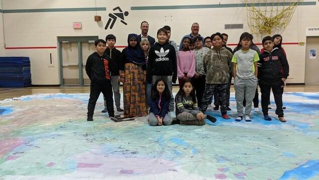 Un enseignant et des élèves debout sur une carte géante.