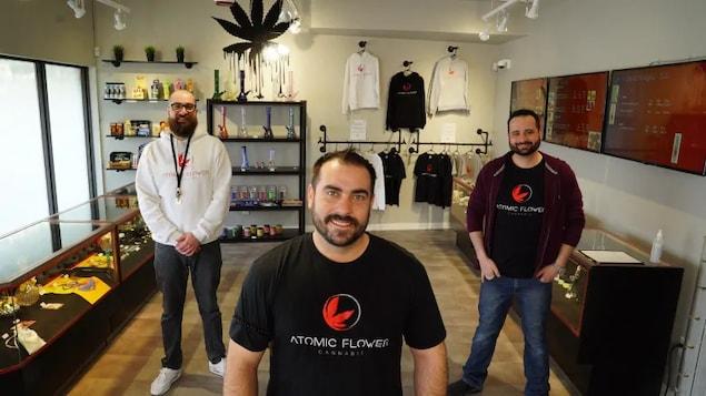Les trois entrepreneurs sont placés de façon symétrique sur la photo, ils forment un triangle. Ils sont debout dans une boutique de cannabis.