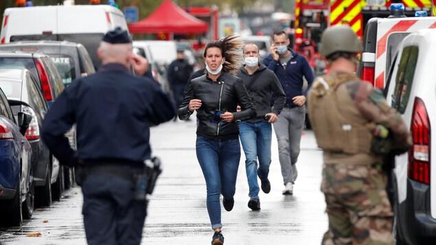 Une femme et deux hommes courent vers des policiers dans une rue.