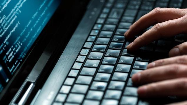 Des mains tapent sur un clavier d'ordinateur.