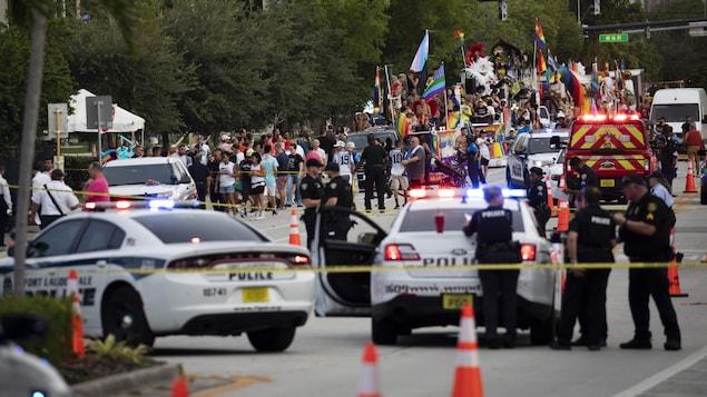 Des policiers et des pompiers encerclant la scène de l'événement, le défilé en arrière-plan.
